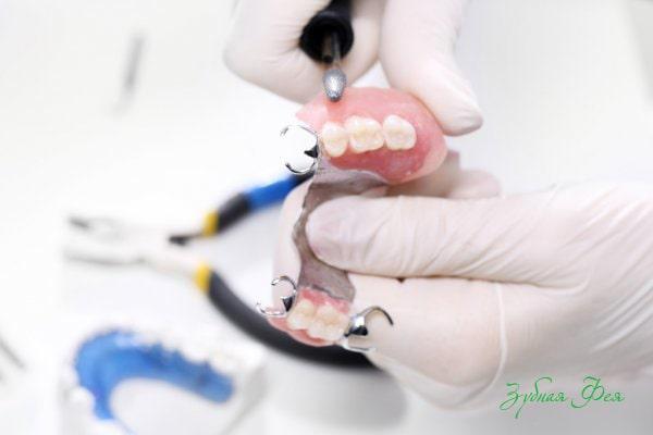 врач держит мост для зубов